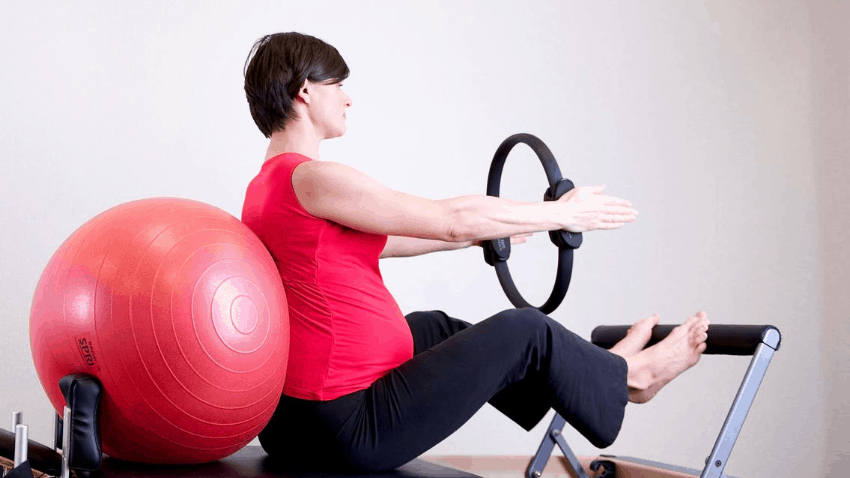 woman with ball and hoop practicing pilates